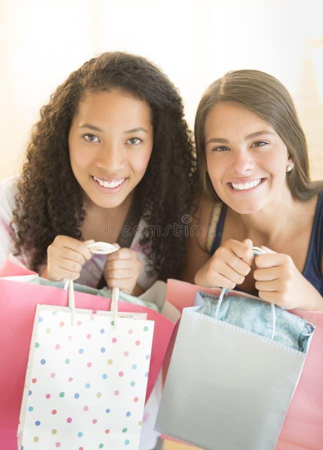 运载购物袋的愉快的十几岁的女孩 图库摄影