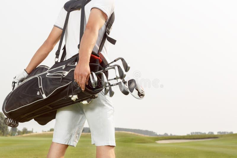运载他的横跨路线的人高尔夫球袋 库存照片