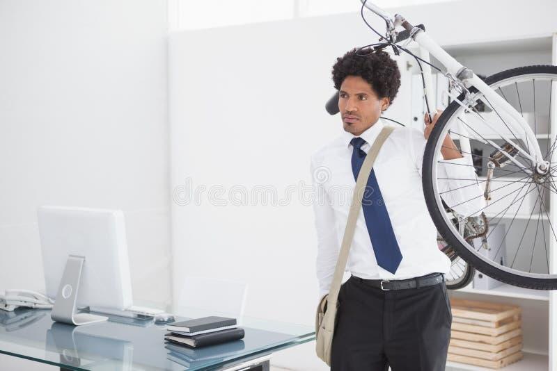 运载他的自行车的可爱的商人 免版税库存图片