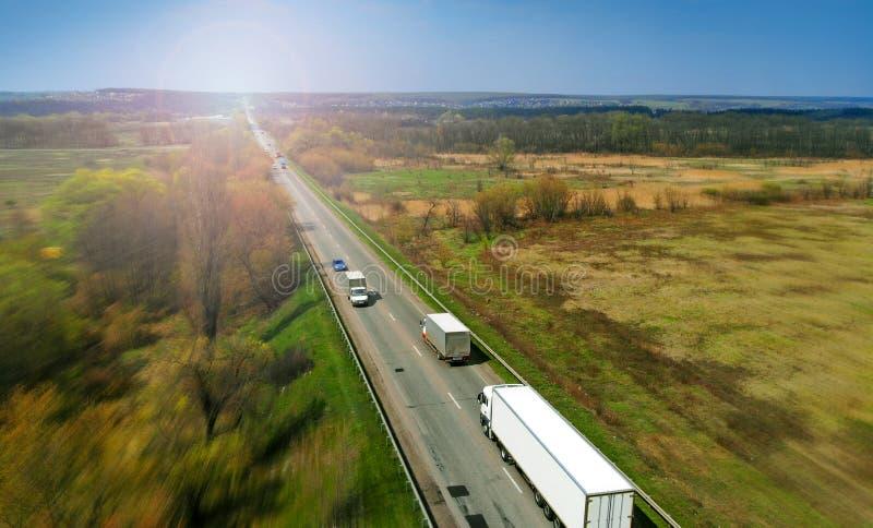 运输与卡车的后勤学背景在领域之间的一条高速公路 免版税库存照片