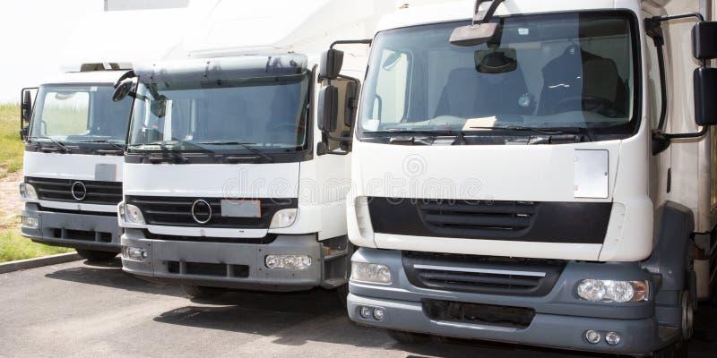 运输业务公司送货服务在工厂仓库发行的van trucks前面 免版税库存照片