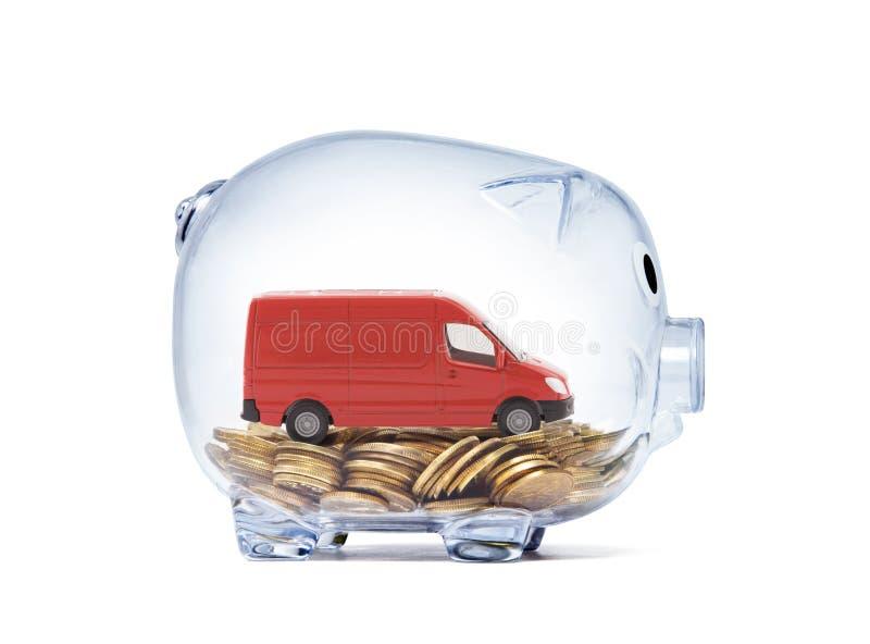 运输在硬币的红色van car在透明存钱罐里面 库存照片