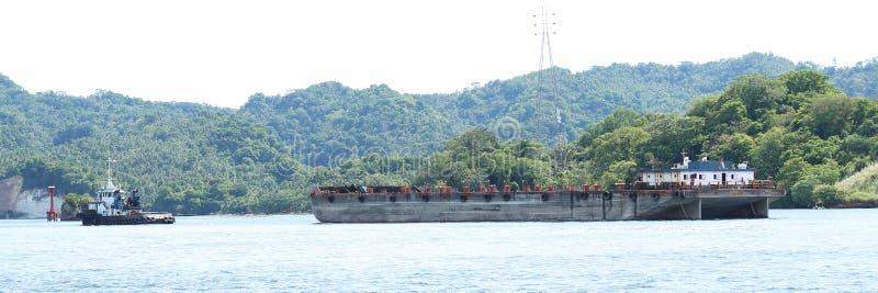 运输船乘拖轮拉扯了在Lembeh海峡 图库摄影