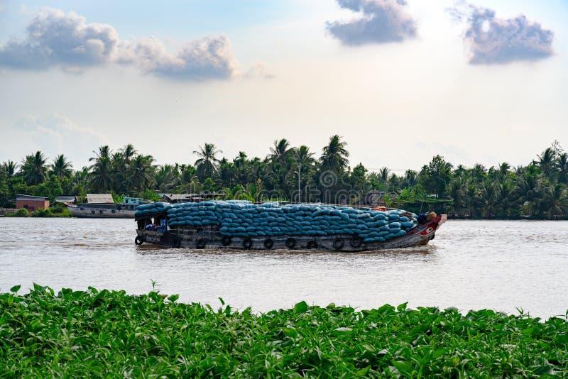 运输袋子在木motorboot的米在distirbutary湄公河 免版税库存图片