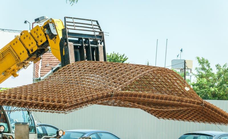 运输金属或钢增强栅格电枢框架的大重的建筑机械铲车对修造的工作地点 图库摄影