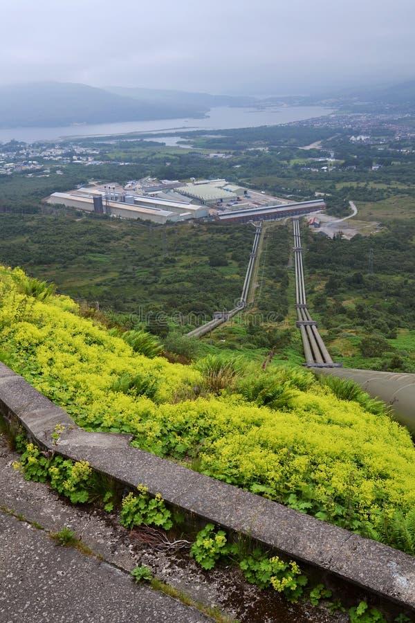 运送水的笔杆对威廉堡铝精炼工植物,海湾Linnhe在背景,多云有雾的天中 库存照片