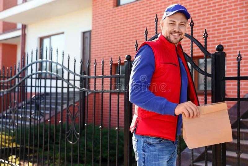 运送食物的男性传讯者在城市 免版税图库摄影