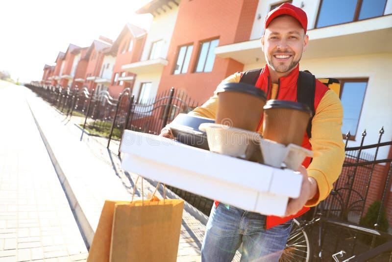 运送食物的男性传讯者在城市 免版税库存照片