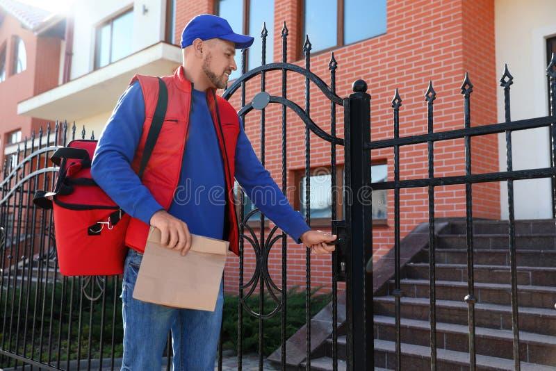 运送食物的男性传讯者在城市 免版税库存图片