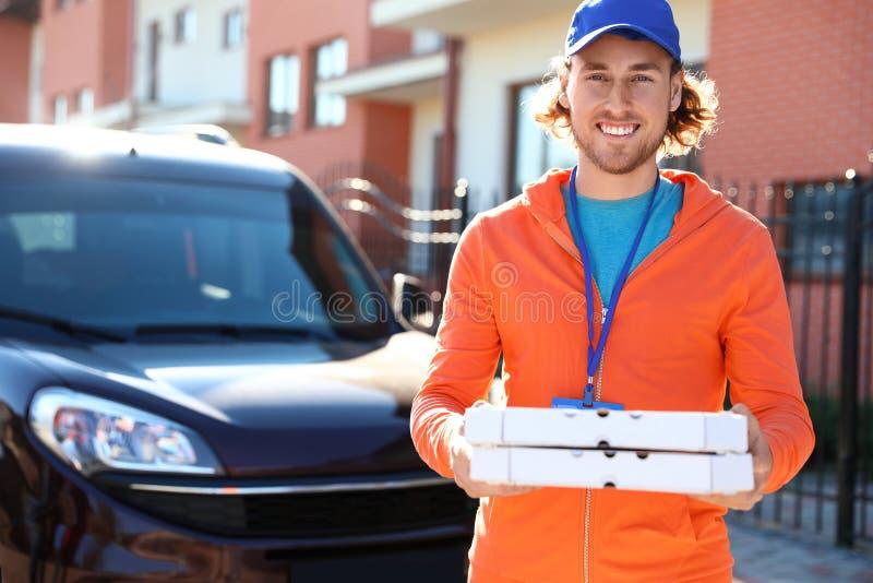 运送食物的男性传讯者在晴朗的城市 免版税库存图片