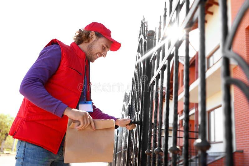 运送食物的男性传讯者在晴朗的城市 库存照片