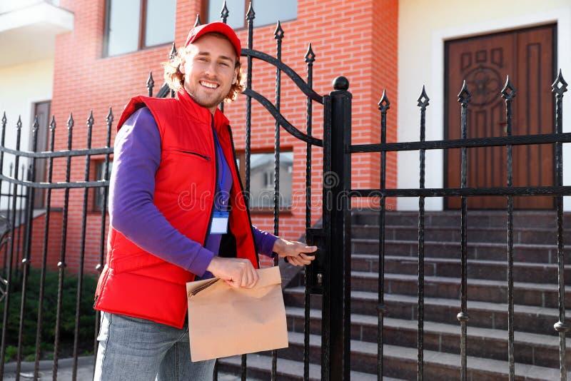 运送食物的男性传讯者在晴朗的城市 库存图片
