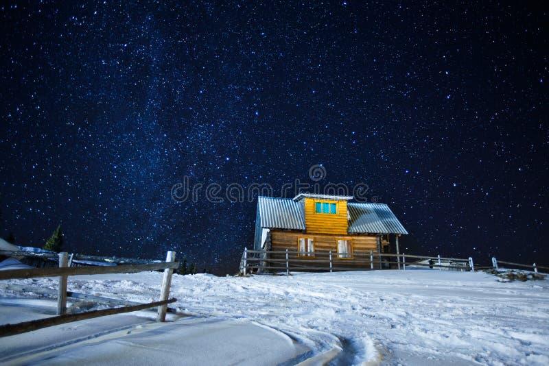 近一个夜冬天满天星斗的天空木房子、长的曝光照片午夜星和多雪的围场的Beautifull风景 库存图片