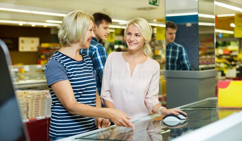 近女性顾客显示用冷冻食品 免版税图库摄影