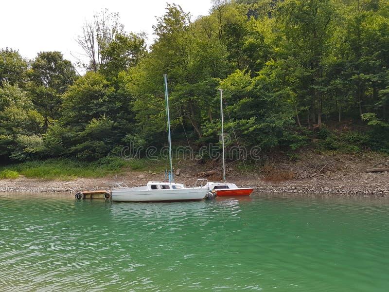 近岸航行小航行游艇被停泊在码头在一个美丽如画的港口 有名望和健康生活方式 Recr 免版税库存照片
