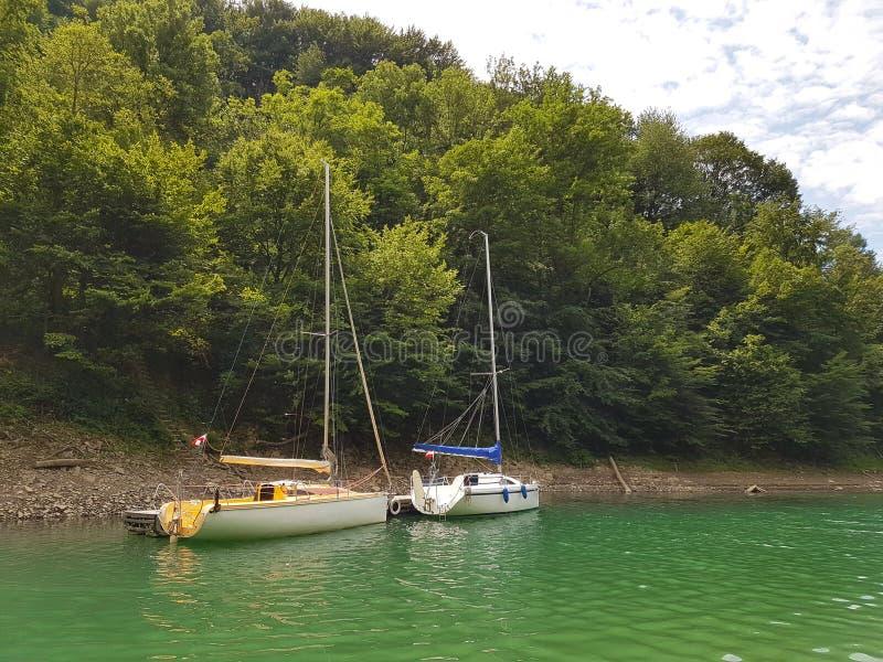 近岸航行小航行游艇被停泊在码头在一个美丽如画的港口 有名望和健康生活方式 Recr 免版税图库摄影
