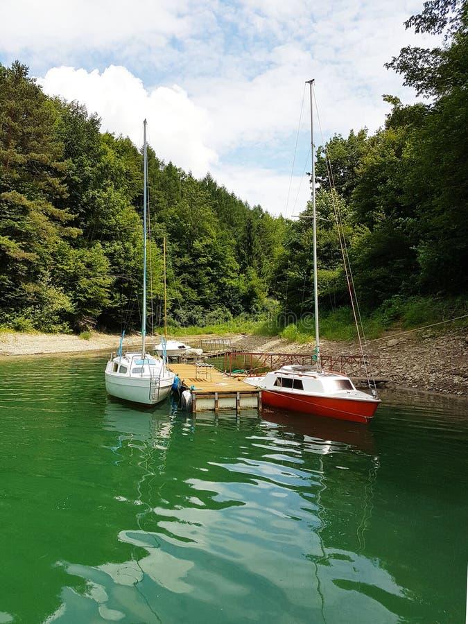 近岸航行小航行游艇被停泊在码头在一个美丽如画的港口 有名望和健康生活方式 Recr 免版税库存图片