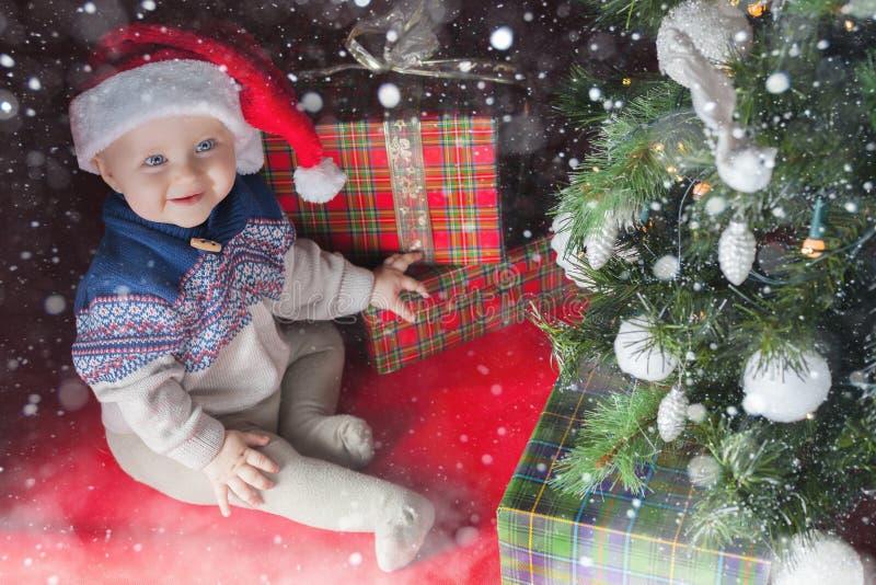 近愉快的婴孩装饰了与许多的圣诞树礼物盒 库存图片