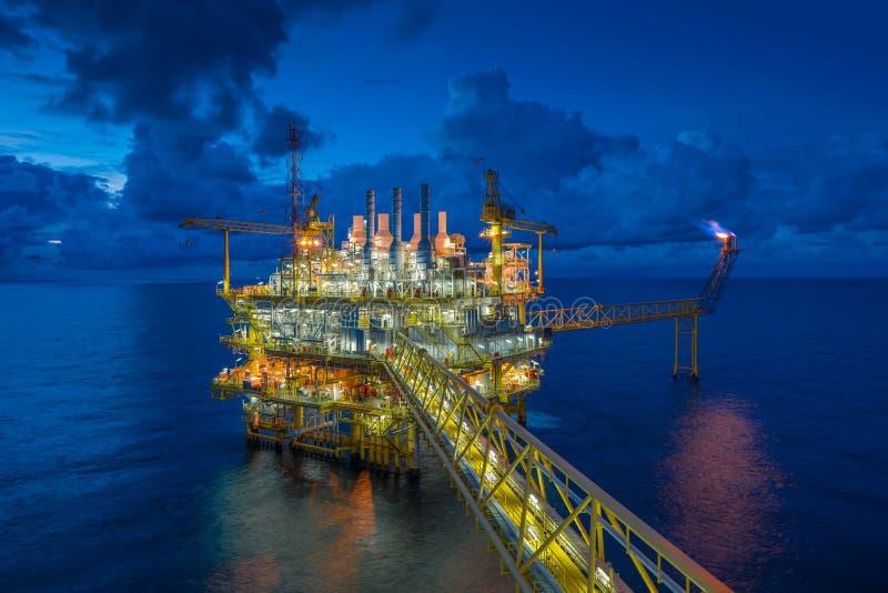 近海处理在日落、力量和能量石油事务的油和煤气平台 免版税库存图片