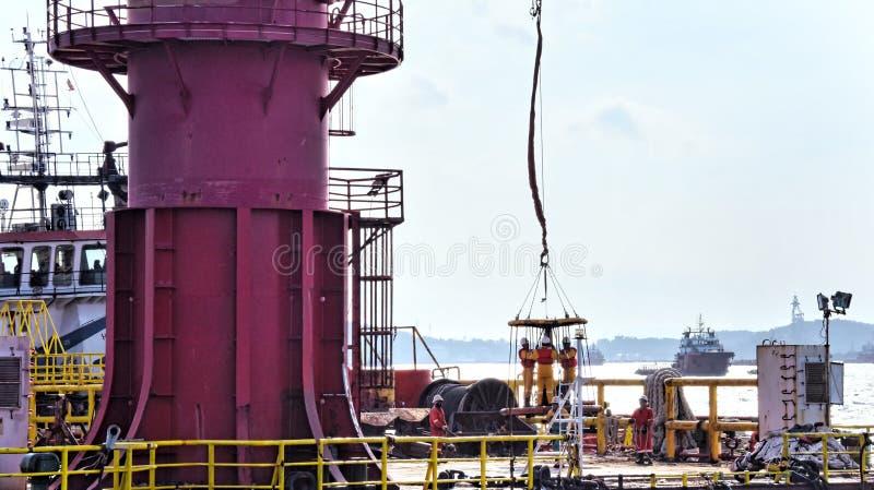 近海工作者准备对上垂悬在天空中的个人安全篮子 免版税图库摄影