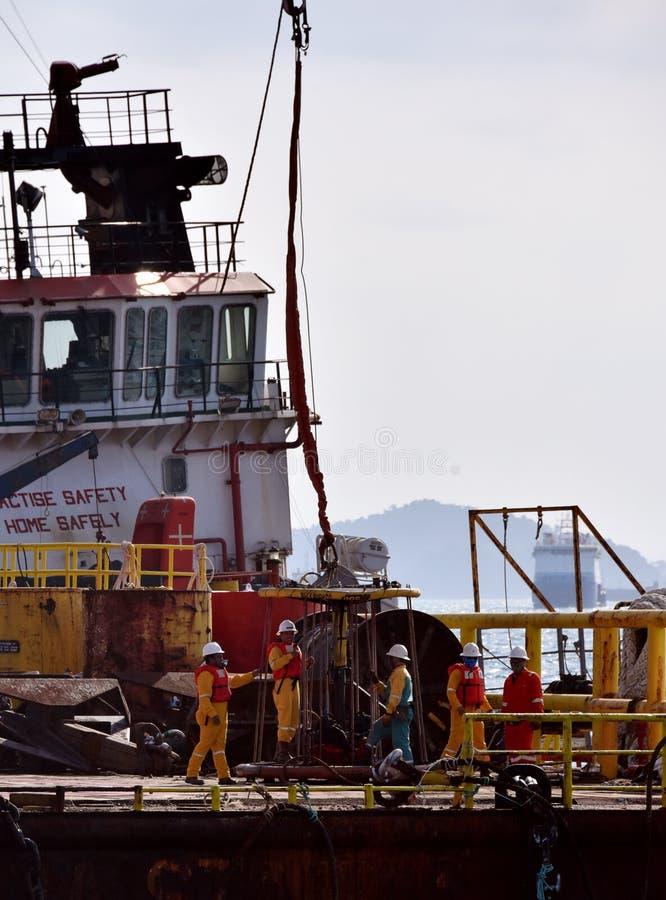 近海工作者准备对上垂悬在天空中的个人安全篮子 库存图片