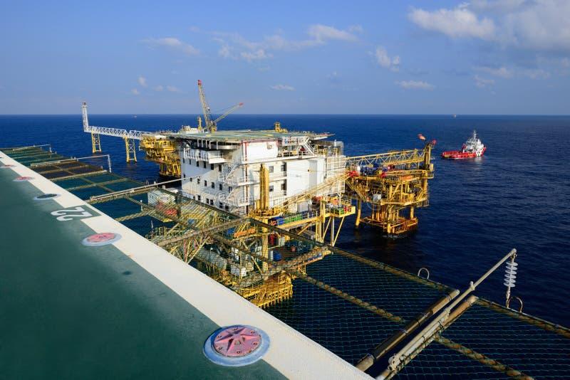 近海抽油装置平台和供应小船 库存图片