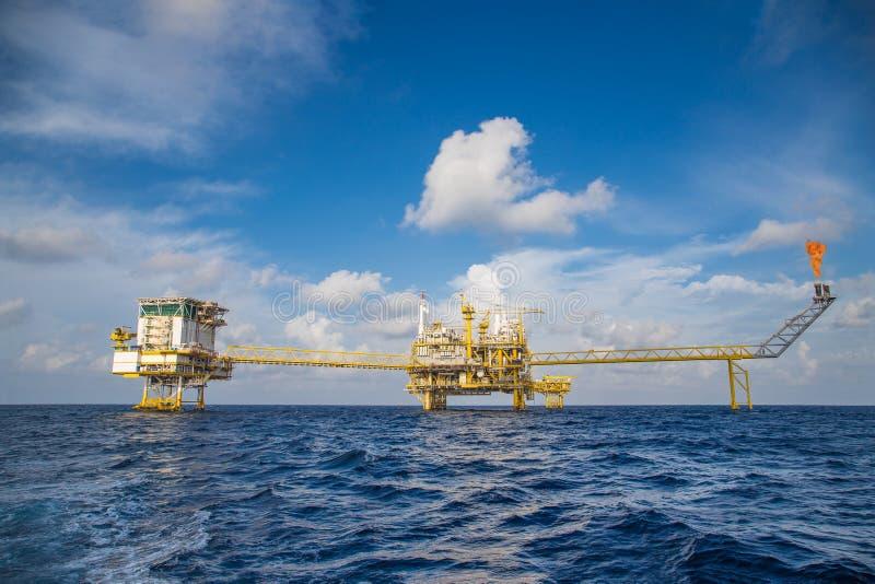 近海油和煤气中央处理平台和适应、火光和遥远的平台 库存图片