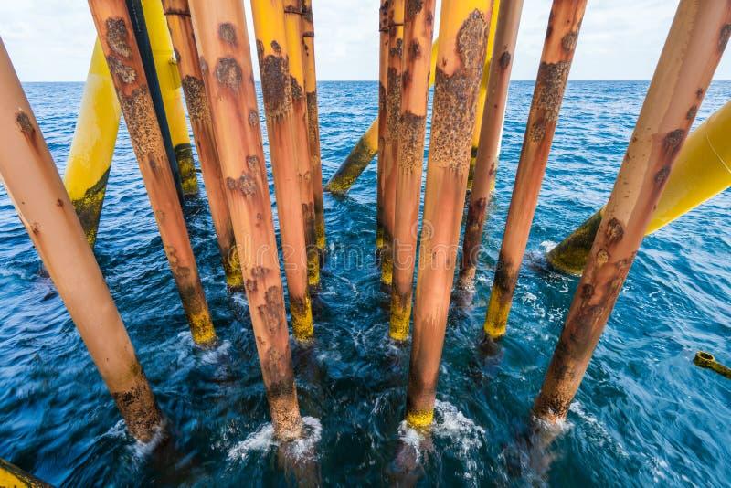 近海油和煤气泉源遥远的平台,被腐蚀的生产管子线 免版税库存图片