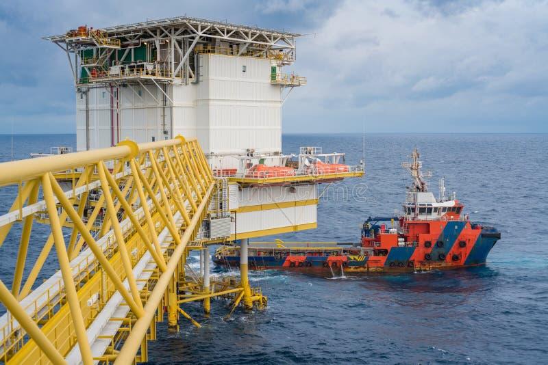 近海油和煤气生产和运输业务,供应小船对适应平台的装货货物 免版税库存图片