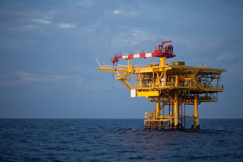 近海油和船具平台在日落或日出时间 生产过程的建筑在海 世界的力量能量 免版税库存照片