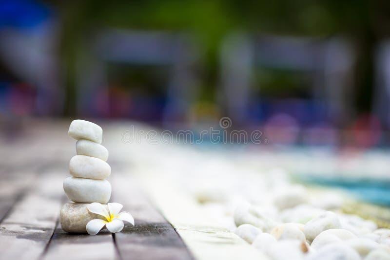近白色平衡的石头和白色羽毛 免版税库存照片