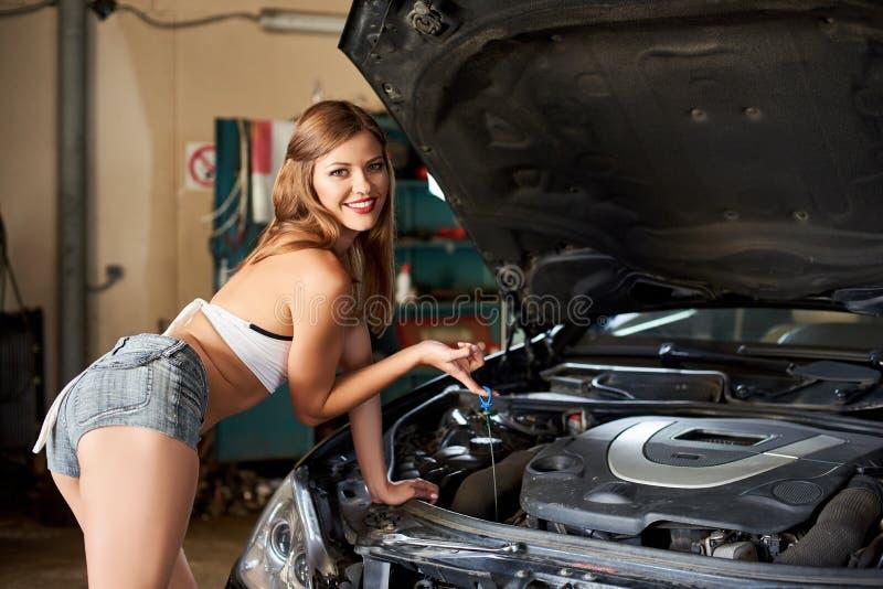 近短的短裤的可爱的女孩打开汽车敞篷  免版税库存照片