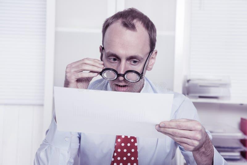 近视在工作-看通过glas的成为秃头的商人 库存图片