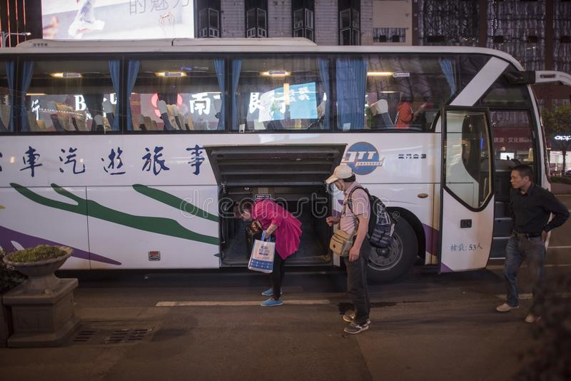 返回从教练的一个对旅游中年夫妇拾起他们的行李,夜视图 库存照片