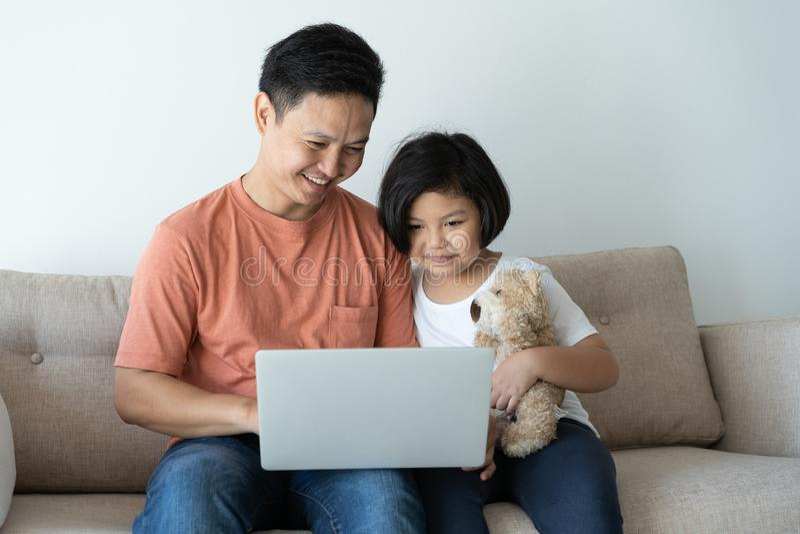 这个亚洲家庭有一个父亲和女儿 他们是愉快的在他们的家的女孩和父亲看膝上型计算机 免版税图库摄影