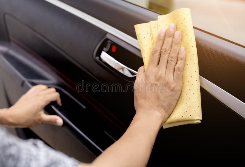 这个图象是抹汽车的图片与一块黄色microfiber布料用人工 免版税库存照片