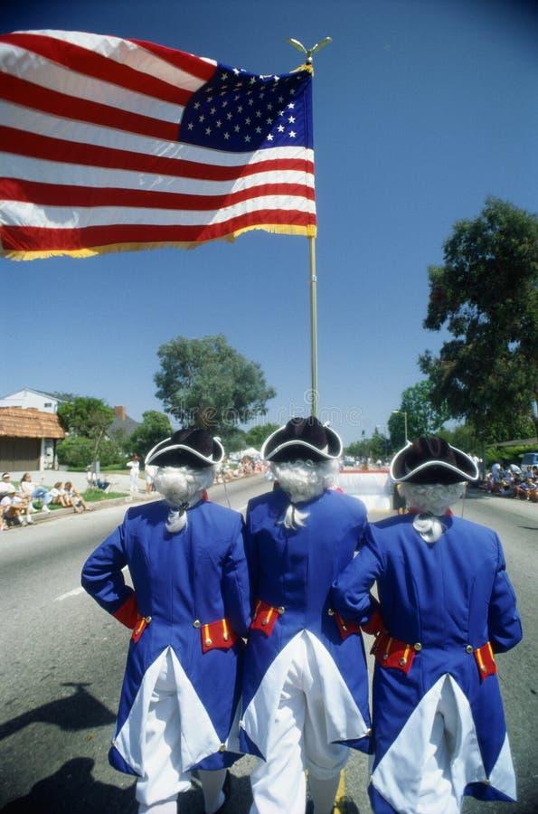 这是与作为革命战争战士打扮的人的一次独立日游行拿着美国国旗 它展示patri 免版税库存图片