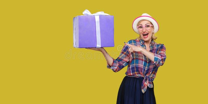 这是你的?愉快的美丽的现代祖母白色帽子的和方格的衬衣身分的,使拿着大礼物盒惊奇与 库存图片