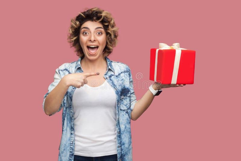 这是你的?蓝色衬衣的愉快的美丽的现代年轻女人有curlty发型身分的,拿着有打开的大礼物盒 库存照片