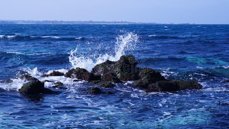 这是波浪碰撞反对Udo一个蓝色海岩石的吻合风景,济州岛 库存照片