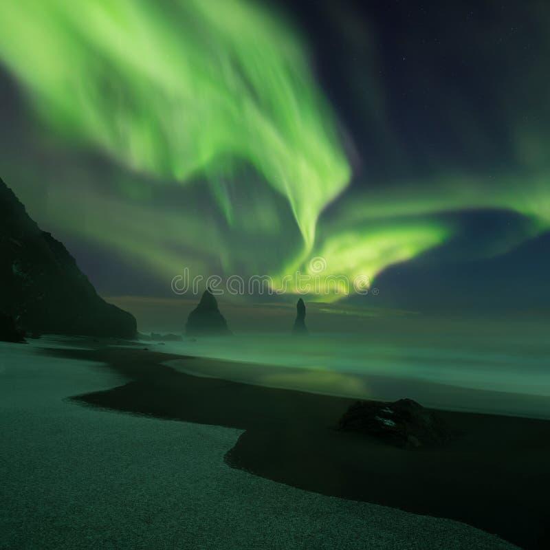 这美丽的北极光或极光borealis在冰岛在rdal VÃk à MÃ的½附近的Reynisdrangar前后被采取了 免版税图库摄影