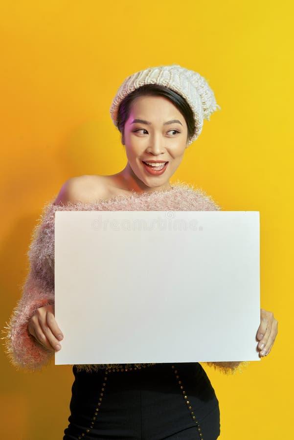 这里您的文本 拿着空的空白的委员会的俏丽的年轻激动的妇女 五颜六色的演播室画象有黄色背景 免版税库存图片