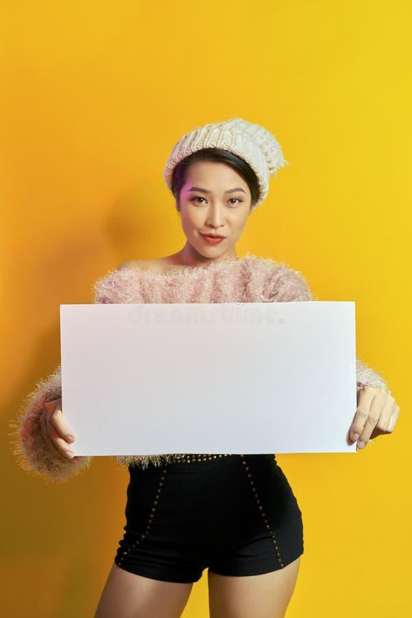 这里您的文本 拿着空的空白的委员会的俏丽的年轻激动的妇女 五颜六色的演播室画象有黄色背景 库存图片
