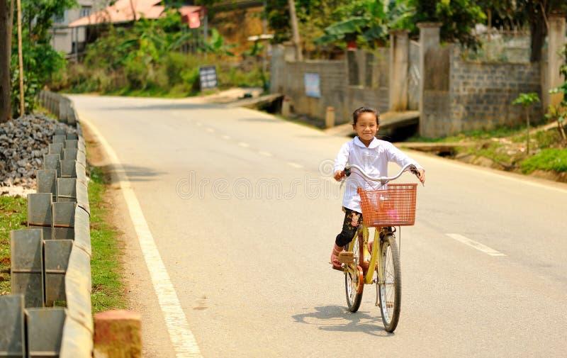 这里的愉快的女孩骑自行车 库存照片