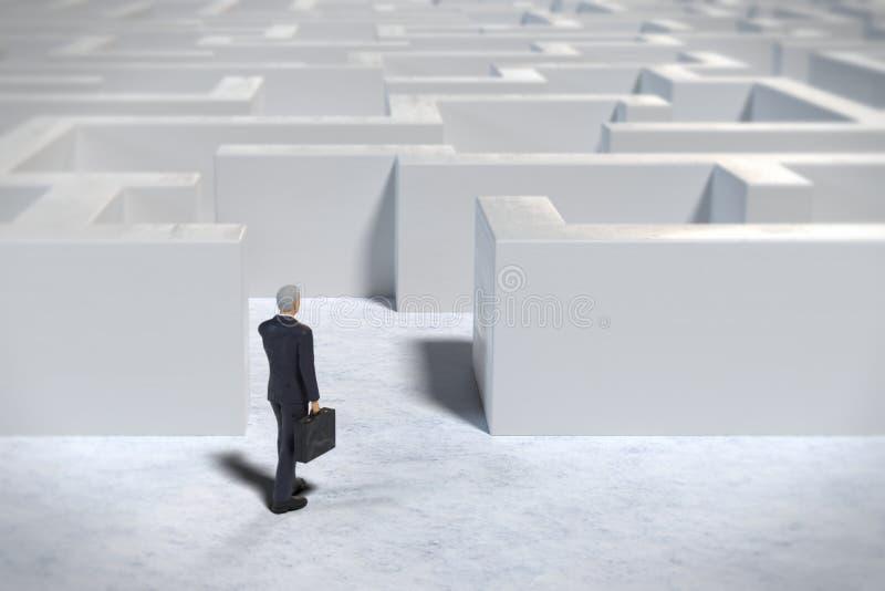 进入一个白色迷宫结构的玩具微型商人小雕象 库存例证