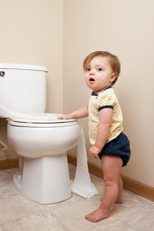进入卫生纸的婴孩 库存图片