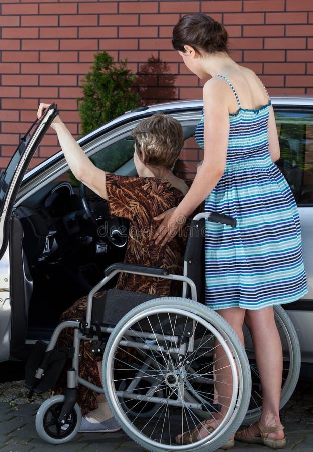 进入汽车的一名残疾年长妇女 免版税库存图片