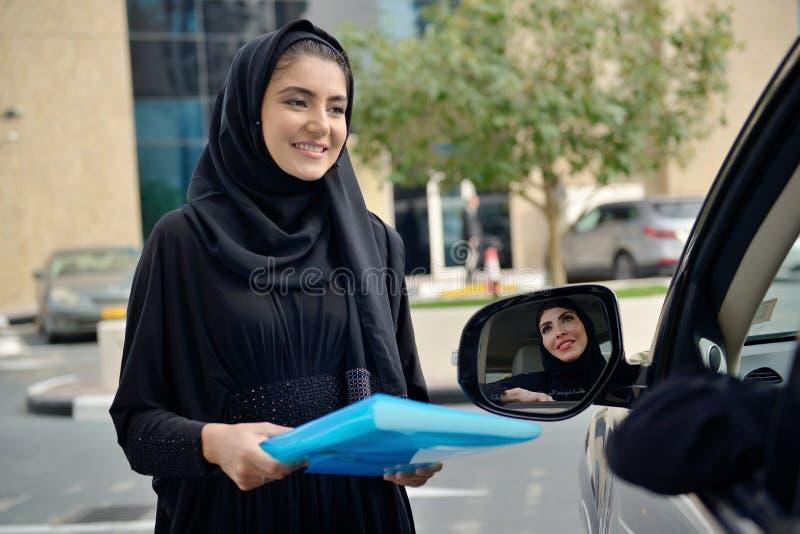 进入汽车的Emarati阿拉伯女商人 免版税库存照片