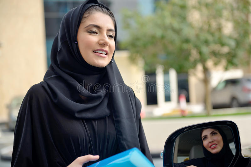 进入汽车的Emarati阿拉伯女商人 库存照片