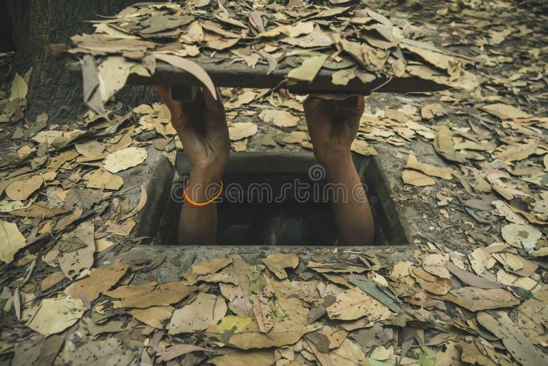 进入狭窄和小古芝池氏隧道的女孩修造由越南游击队在越南战争,从胡志明市的60 km期间 免版税库存照片